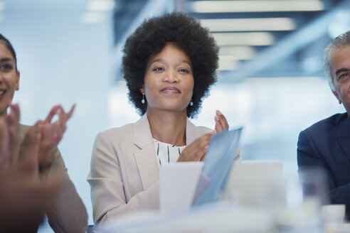 Confident businesswoman clapping in conference room meeting - HOXF04301