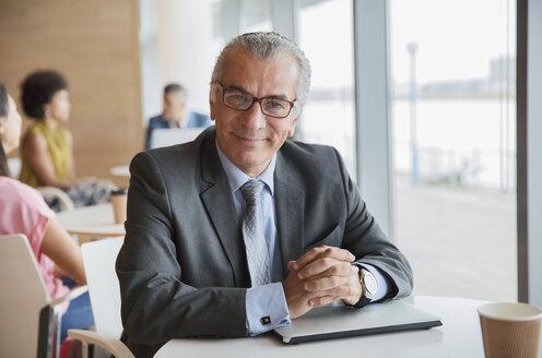 Portrait confident businessman in cafeteria - HOXF04316