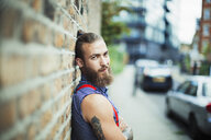 Confident male hipster on urban sidewalk - CAIF22428