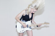 Young woman playing electric guitar - CAIF22443