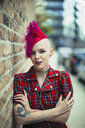 Portrait confident young woman with pink mohawk on urban sidewalk - CAIF22455