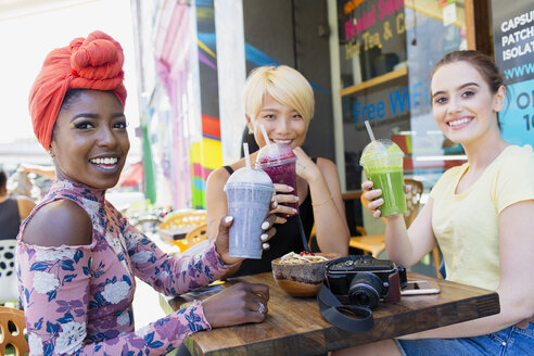 Portrait smiling young women friends drinking smoothies at sidewalk cafe - CAIF22467