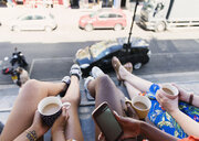 Women friends drinking coffee, dangling legs out urban apartment window - CAIF22473
