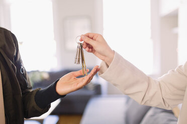 Real estate agent giving keys to homeowner - CAIF22485