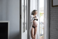 Pretty blonde pregnant woman standing at the window holding cup of tea - IGGF00721