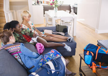 Young women friends with bags arriving at house rental - CAIF22489