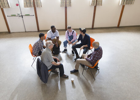 Men talking in group therapy circle - CAIF22516