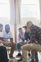 Men with digital tablet talking in group therapy circle - CAIF22522