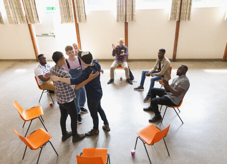 Men hugging and clapping in group therapy - CAIF22528