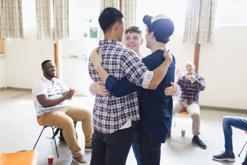 Men hugging in group therapy - CAIF22552