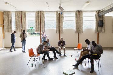 Men waiting, using smart phones in community center - CAIF22558