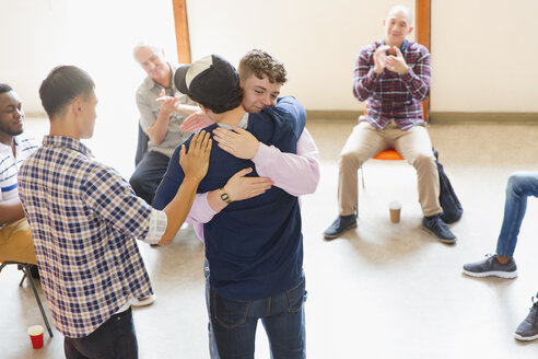 Men hugging and clapping in group therapy - CAIF22564