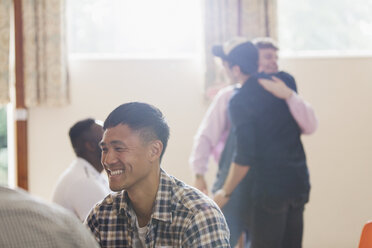 Smiling man enjoying group therapy - CAIF22567