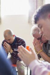 Men praying with prayer beads in prayer group - CAIF22573