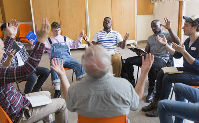 Men praying with arms raised in prayer group - CAIF22582