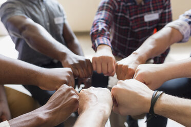 Men joining fists in circle in group therapy - CAIF22585