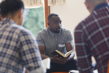 Attentive young man with bible in prayer group - CAIF22588