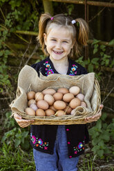 Smiling girl holding basket with eggs, looking at camera. - MINF09834