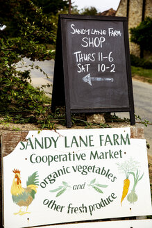 Close up of Sandy Lane farm shop sign and blackboard with opening times. - MINF09870