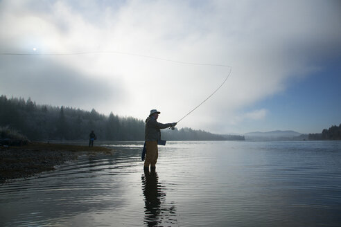 Silhouette of fisherman fly fishing for salmon and sea run cutthroat trout - MINF09876