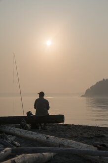 A fly fisherman taking a break from fly fishing relaxing by the water - MINF09885