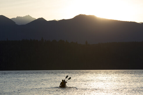 A couple sitting in a sit-on- top Kayak paddling in Puget Sound near the Olympic Mountains in Washington State, USA. - MINF09897