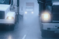Partial view of large commercial truck driving in hazardous conditions of snow and rain on a freeway. - MINF09942