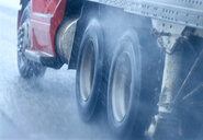 Partial view of large commercial truck driving in hazardous conditions of snow and rain on a freeway. - MINF09945