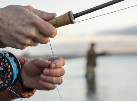 A closeup of a fly fisherman's hands holding his fly rod and line while fishing. - MINF10050