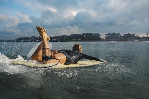Indonesia, Bali, Canggu, female surfer lying on surfboard - KNTF02591