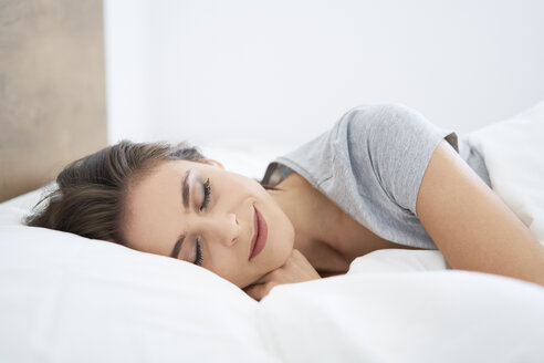 Young woman resting on bed, with eyes closed - BSZF00804