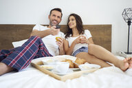 Happy couple having breakfast in bed, watching TV - BSZF00831