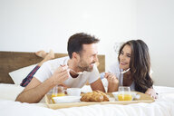 Happy couple having breakfast in bed - BSZF00834