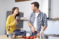 Affectionate couple in kitchen, preparing spaghetti toghether, drinking red wein - BSZF00843