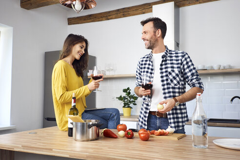 Affectionate couple in kitchen, preparing spaghetti toghether, drinking red wein - BSZF00846