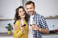 Happy couple standing in kitchen, with arms around, drinking red wine - BSZF00852