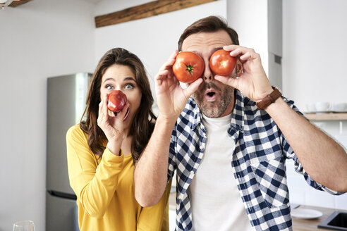 Couple having fun in the kitchen, playing with tomatoes - BSZF00855