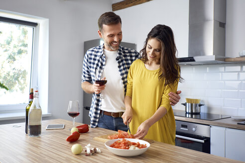 Affectionate couple in kitchen, preparing spaghetti toghether, drinking red wein - BSZF00861
