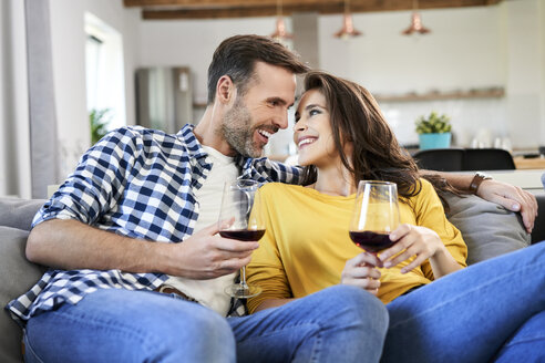 Happy couple sitting in living room, drinking red wine - BSZF00864