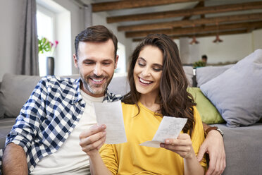 Couple sitting in living room, checking bills - BSZF00870