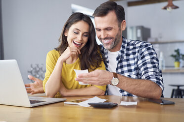 Couple sitting at dining table, using laptop, checking bills - BSZF00873