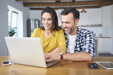 Couple sitting at dining table, using laptop, smiling - BSZF00876