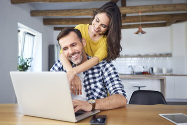 Happy couple sitting at dining table, embracing, using laptop - BSZF00879