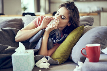 Portrait of young woman lying sick with the flu on sofa and blowing nose - BSZF00894