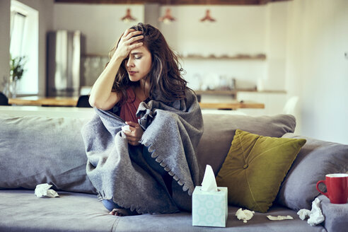 Portrait of sick woman sitting on couch and holding her aching head - BSZF00897