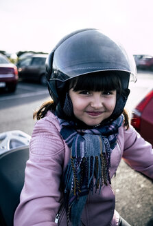 Portrait of smiling little girl on a motorcycle wearing helmet and pink leather jacket - MGOF03925