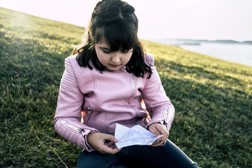 Portrait of girl wearing pink leather jacket sitting on a meadow looking at labelled paper - MGOF03937