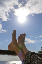 Feet of a girl leaning on railing at backlight - BFRF01967