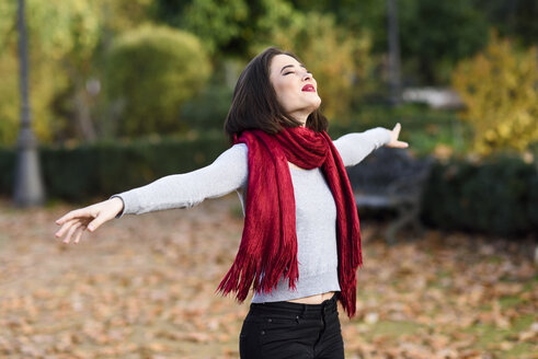 Happy young woman wearing red scarf in autumn - JSMF00731