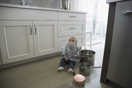 Baby boy playing with pots and pans on kitchen floor - HEROF04136